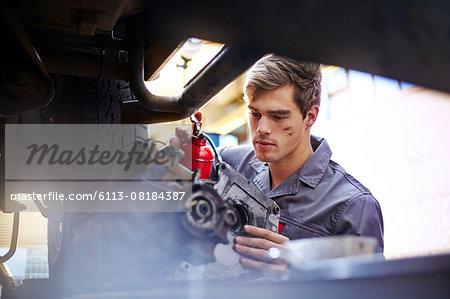 Mechanic oiling part in auto repair shop