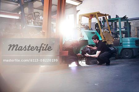 Mechanics examining forklift in auto repair shop