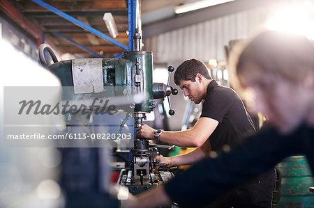 Mechanics using machinery in auto repair shop