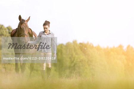 Woman walking horse in rural field
