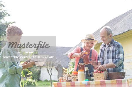 Grandparents and grandson preparing to sell honey