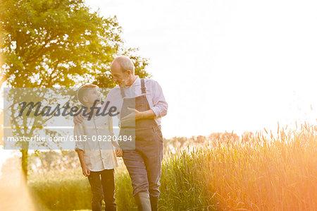 Grandfather farmer talking to grandson in sunny rural wheat field