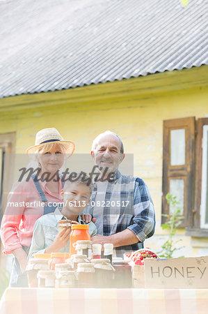 Portrait proud grandparents and grandson selling honey at farmer's market stall