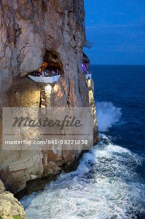 Bar built in cliff caves, Cova d'en Xoroi in evening, Cala en Porter, Menorca, Balearic Islands, Spain, Mediterranean, Europe