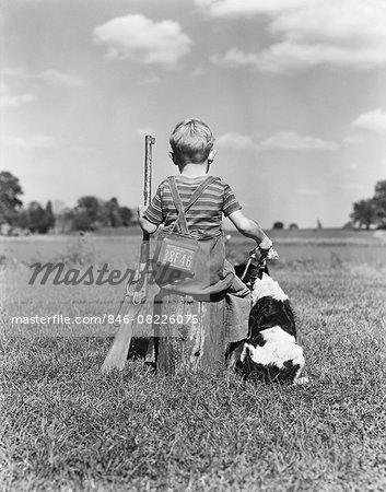 1940s BACK VIEW OF BOY WEARING HUNTING PERMIT HOLDING BB GUN SITTING ON TREE STUMP NEXT TO SPRINGER SPANIEL DOG
