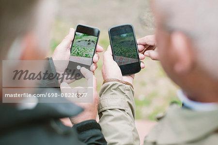 Cropped image of senior men using smart phones outdoors