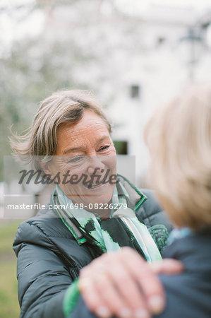 Happy senior woman talking to friend at park