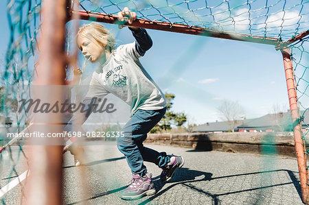 Girl playing hockey at yard against sky