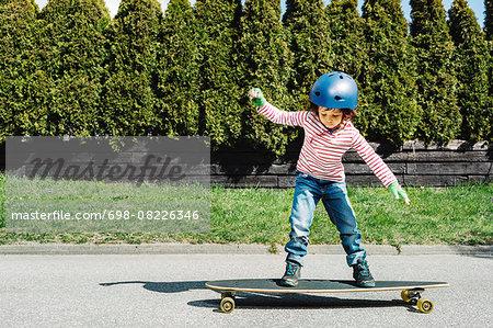 Full length of boy balancing on skateboard at yard