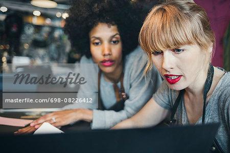 Mid adult female mechanics using laptop in workshop