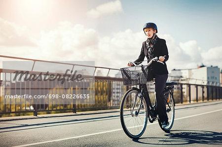 Businesswoman riding bicycle on bridge in city
