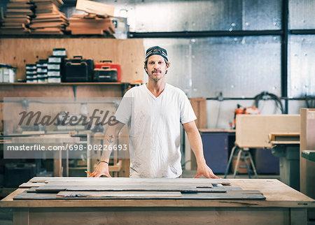 Portrait of confident carpenter standing at workbench in workshop