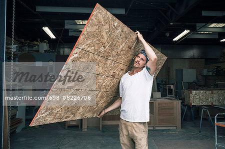 Carpenter carrying wooden plank at workshop