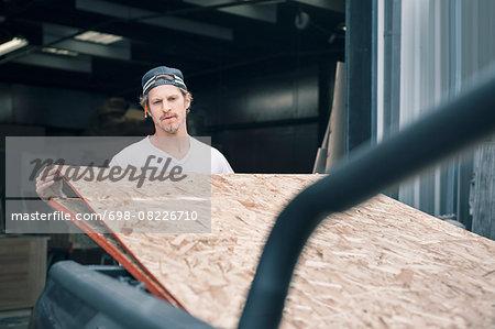 Carpenter loading wooden planks in pick-up truck