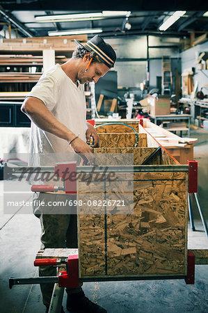 Side view of carpenter making furniture at workshop