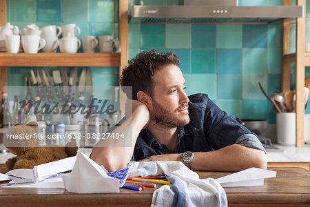 Man daydreaming in kitchen