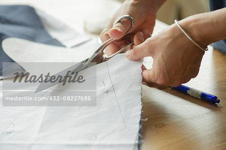 Woman cutting fabric, cropped