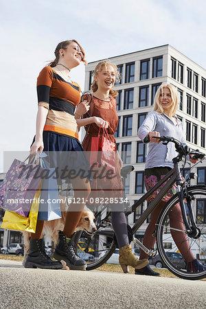 Three friends walking in a playground with dog, Munich, Bavaria, Germany