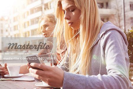 Teenage girl text messaging at sidewalk cafe, Munich, Bavaria, German