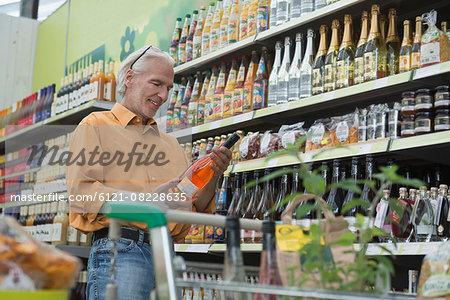 Customer reading label of wine bottle in supermarket, Augsburg, Bavaria, Germany