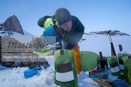 Man preparing ready meals to the bivouac camp, Tyrol, Austria