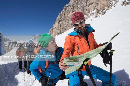 Ski mountaineers reading map while climbing on snowy mountain, Val Gardena, Trentino-Alto Adige, Italy