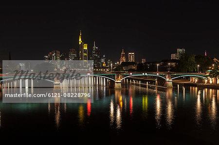 Bridge over river with skyline lit up at night, Frankfurt, Germany