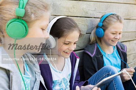 Three friends sitting in playground and listening music, Munich, Bavaria, Germany