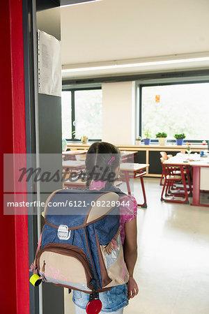 Rear view of a schoolgirl entering in classroom, Munich, Bavaria, Germany