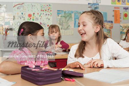 Schoolgirls talking in classroom, Munich, Bavaria, Germany