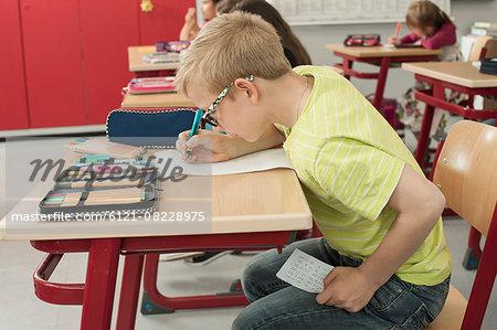 Schoolboy cheating on a test in classroom, Munich, Bavaria, Germany
