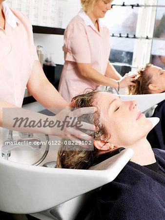 Hairdressers washing women's hair