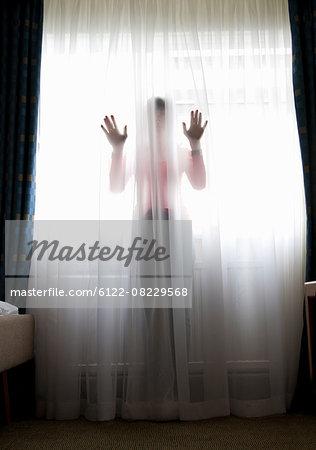 Woman standing behind sheer curtain