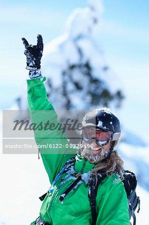 Skier making hand gesture in snow