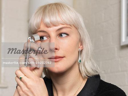 Female jeweler examining diamond using magnifier in jewellery shop