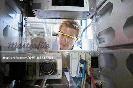 Factory technician inspecting machine electronics