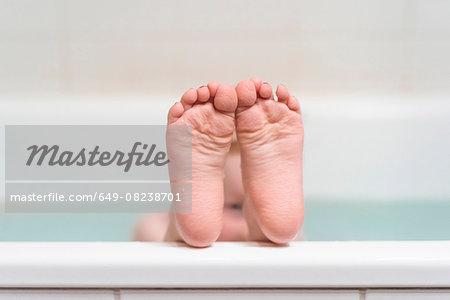 Young girl with feet on edge of bathtub