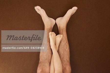 Child's legs on man's legs