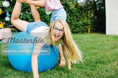 Girl balancing on fitness ball in garden