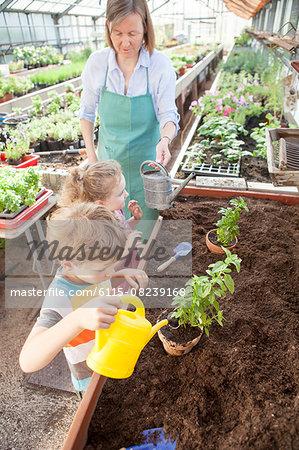 Female gardener and children in greenhouse