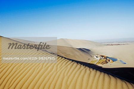 Ming Sha sand dunes and pavilion at Crescent Moon Lake, Dunhuang, Gansu Province, China, Asia