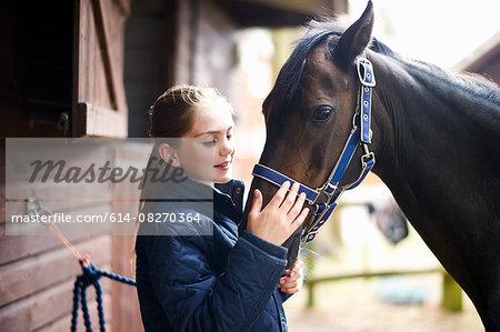 Girl horseback rider petting horse
