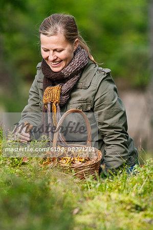 Smiling woman picking chanterelles