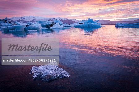 Iceland, Jokulsarlon Glacier Lagoon, icebergs and ice chunk at sunset