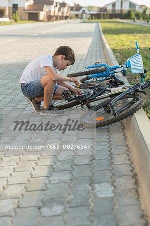 Side view of boy repairing bicycle on footpath