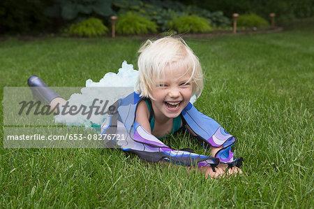 Happy girl lying on grassy field in backyard