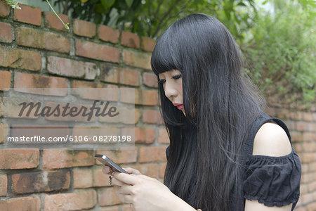 Young Harajuku woman using cell phone