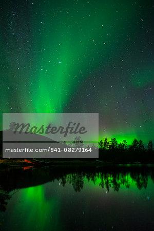 Aurora Borealis and stars over lake at night, Muonio, Lapland, Finland, Scandinavia, Europe