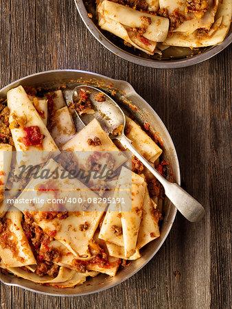close up of rustic italian pasta in ragu sauce