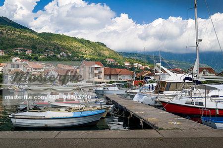 Tivat local fisherman's boats marina. Old traditional boats and contemporary sailing yachts moored at pier. Montenegro